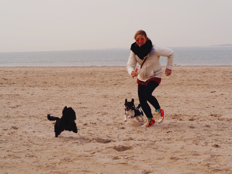 blond girls running on the beach with dogs